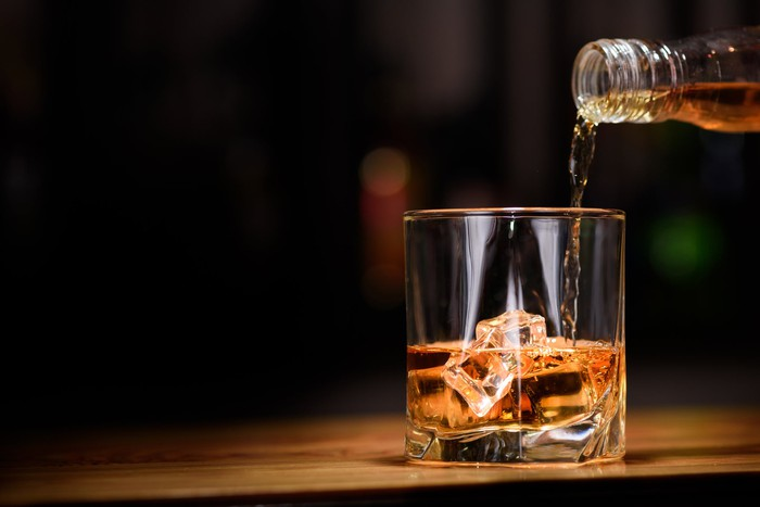 Bottle of bourbon, whiskey being poured into a glass with ice.