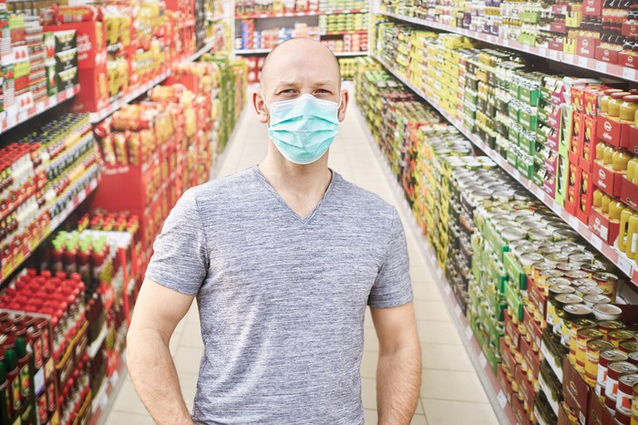 A man in a grocery store wearing a protective face mask.