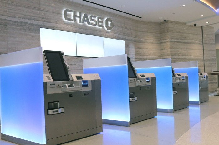 Automated teller machines at a Chase branch with marbled white floors and walls and the Chase logo.