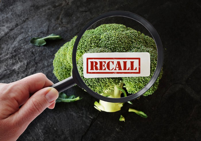 A hand holding a magnifying glass, looking at broccoli, with a Recall label superimposed.