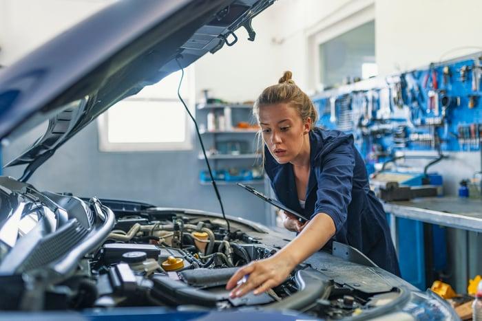 An auto mechanic assessing a car's engine.