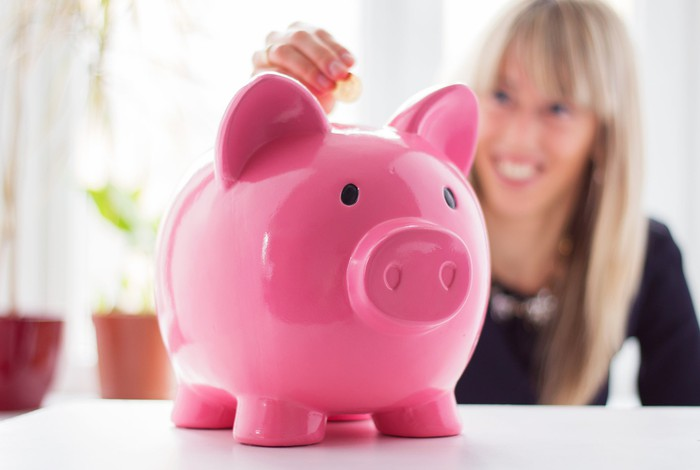 A woman adding a coin to a piggy bank.