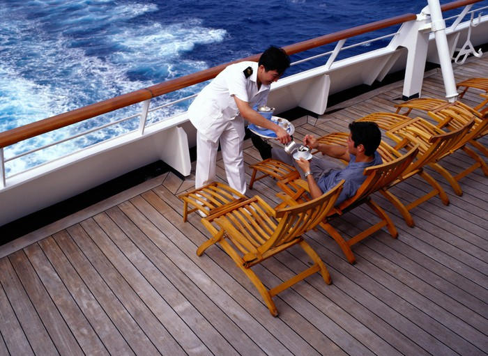 A waiter on a cruise ship serves coffee to a passenger lounging on the back.