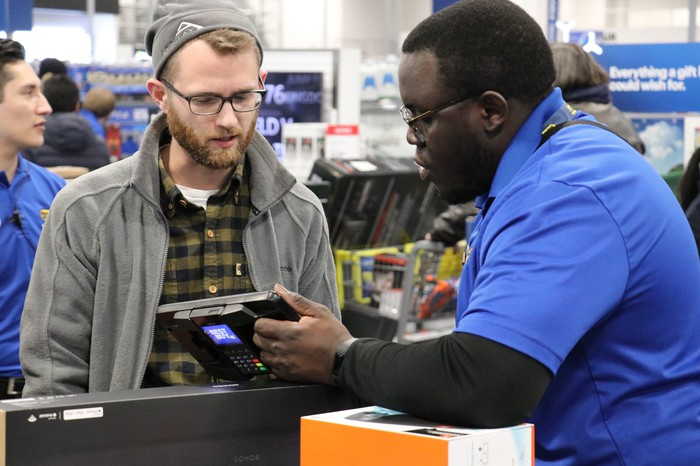 Best Buy employee assisting a customer.