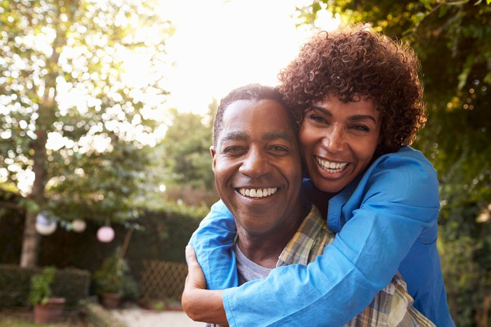 Mature couple smiling and hugging in backyard