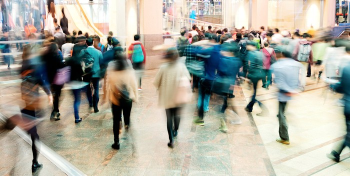 A blurry image of shoppers passing through a mall