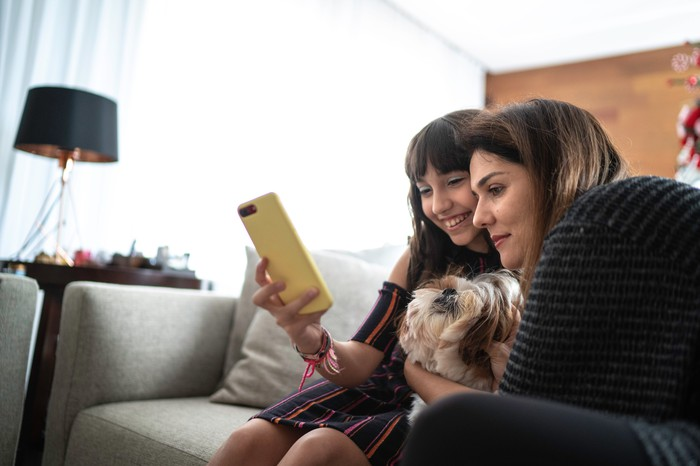 A woman with her daughter sitting on a couch and looking at an iPhone.