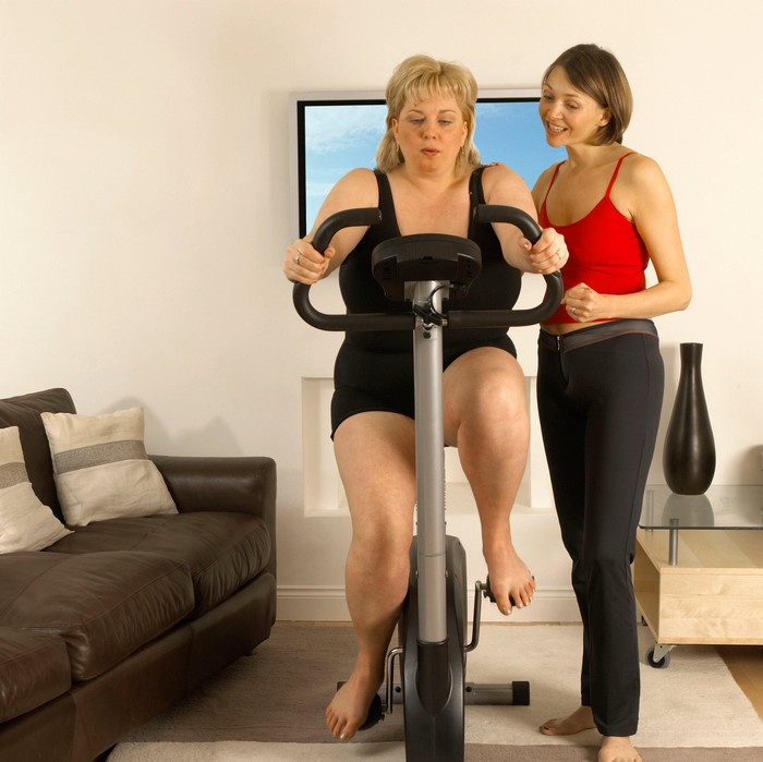 Woman in red standing beside a woman in black, who is using a home exercise bike.