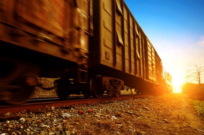 Freight train boxcars heading down a track into sunset