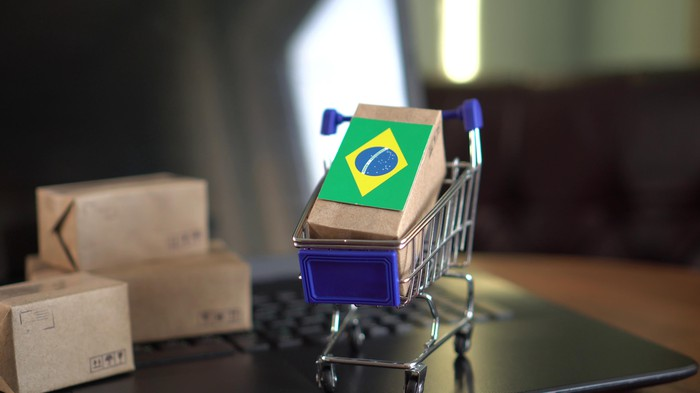 A small shopping cart sits on a laptop with a package in it draped with a Brazilian flag.
