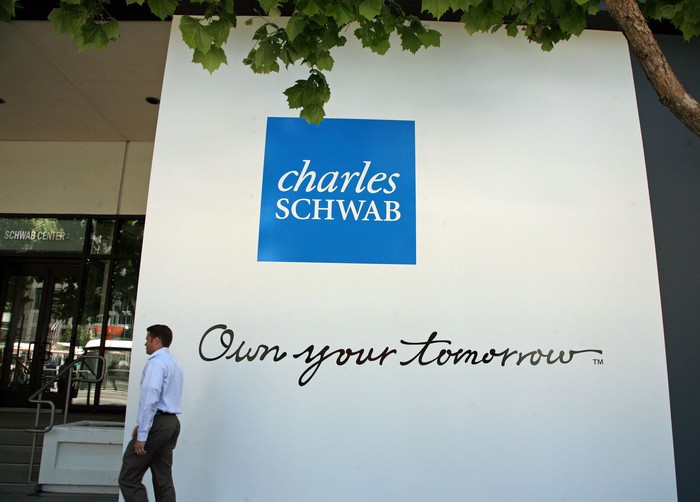 A man walking past Charles Schwab branding on a building.