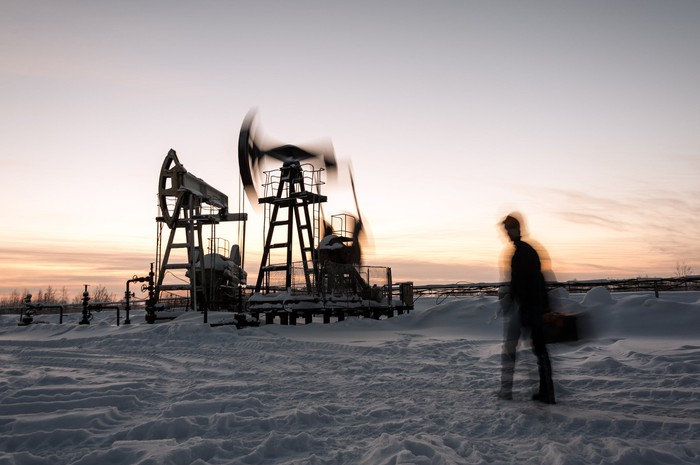 Oil pumps in motion with a person walking by and snow on the ground.