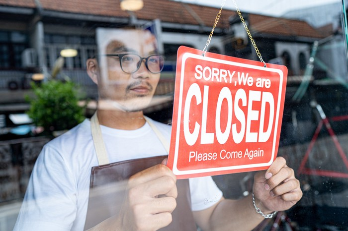 """A man puts up a """"Sorry, we are closed"""" sign in his shop window."""