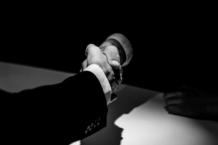 Black and white photo of two businessmen shaking hands over a table.