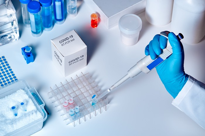 A person's hand wearing a glove and holding a syringe as the person tests a COVID-19 sample.
