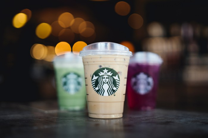 Several Starbucks beverages on a countertop.