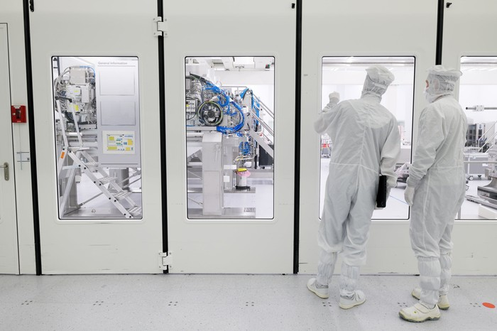 Two engineers in clean room suits look through a window into a manufacturing room of heavy equipment.
