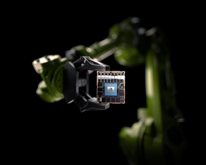 A robotic arm holding an NVIDIA chip.