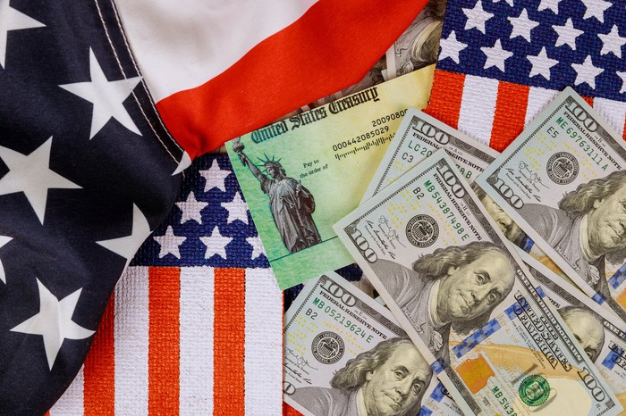 A stimulus check amid hundred-dollar bills and U.S. flags.