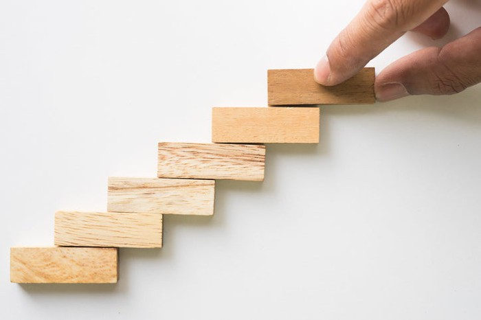 A hand placing wooden blocks in an ascending stair pattern.