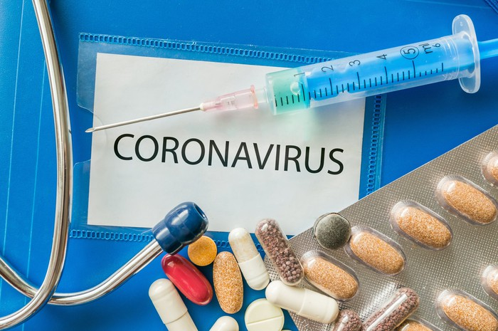 """An injection, pills, and a stethoscope are seen against a blue background with the word """"coronavirus"""" written on it."""