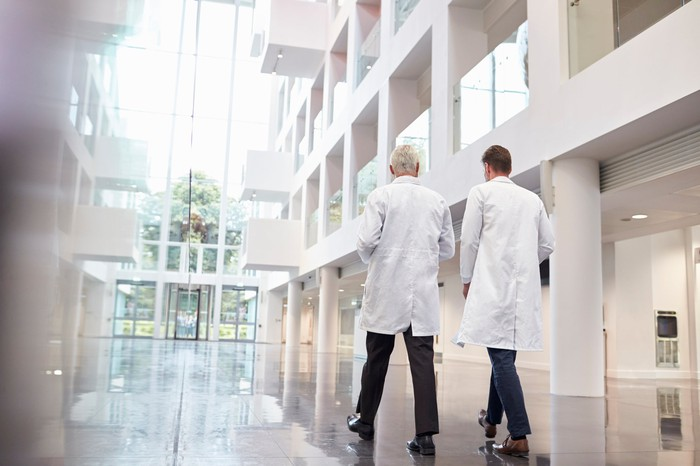 Two people in white lab coats walking through an atrium in a white multi-story building.