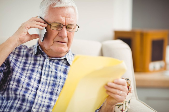 Older man holding phone to ear while holding document