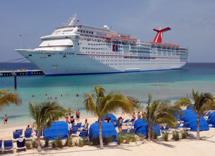 The Carnival ship Elation sits in dock in the Grand Turks with beachgoers standing in the foreground.