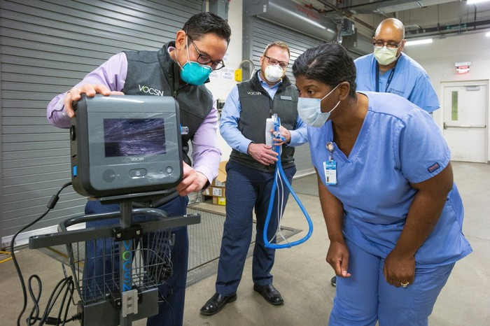 Healthcare workers examine a VOCSN ventilator produced by the Ventec-GM joint venture.