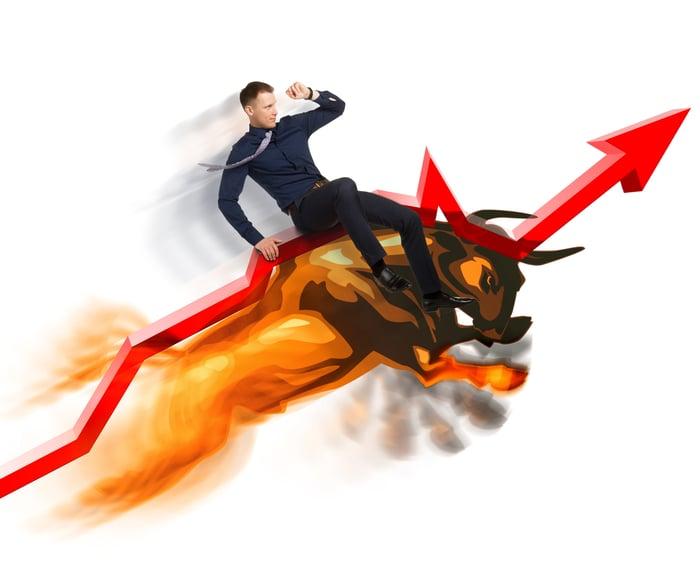 Man rides a bull up a rising stock arrow.