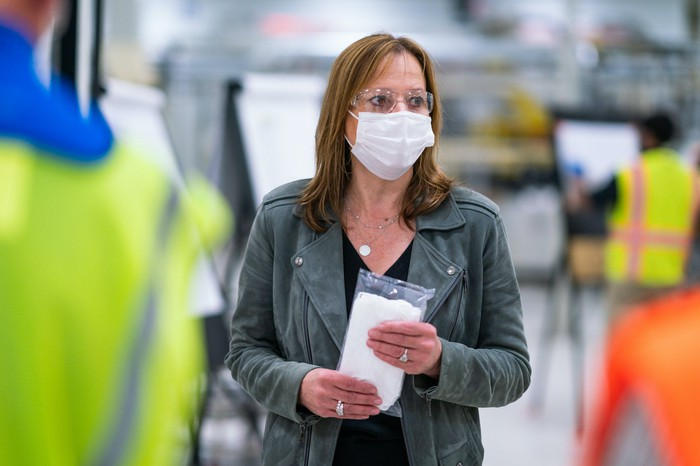 GM CEO Mary Barra, wearing a mask and eye protection, is shown on the floor of a GM factory making masks for first responders.