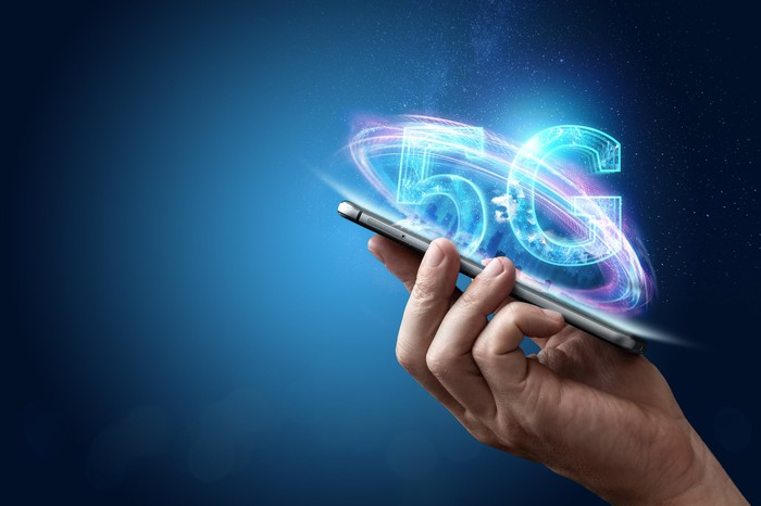 A hand holding a smartphone with digital images of 5G emerging from the device