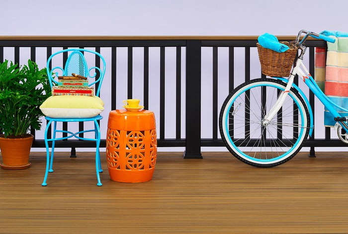 Deck and railing products made using Trex composites. A colorful bike and bistro chair are on the patio deck.