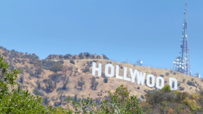 Hollywood sign on side of hill with radio tower nearby.