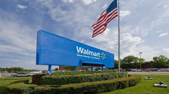 Walmart sign next to an American flag