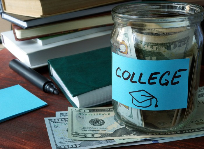 Jar filled with bills labeled college on table with bills under it, sitting next to books, a pen, and a notepad