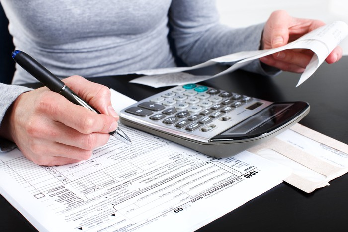 A person checking receipts and using a calculator to fill out a paper tax form.