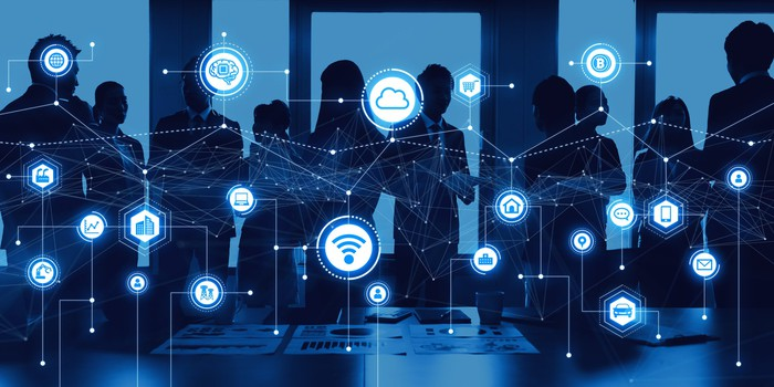 Image of digital transformation ecosystem superimposed over silhouettes of professionals standing.