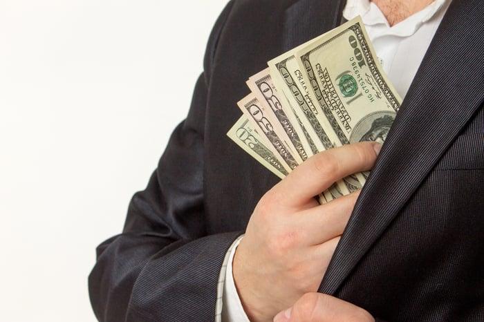 Man putting hundred dollar bills in pocket