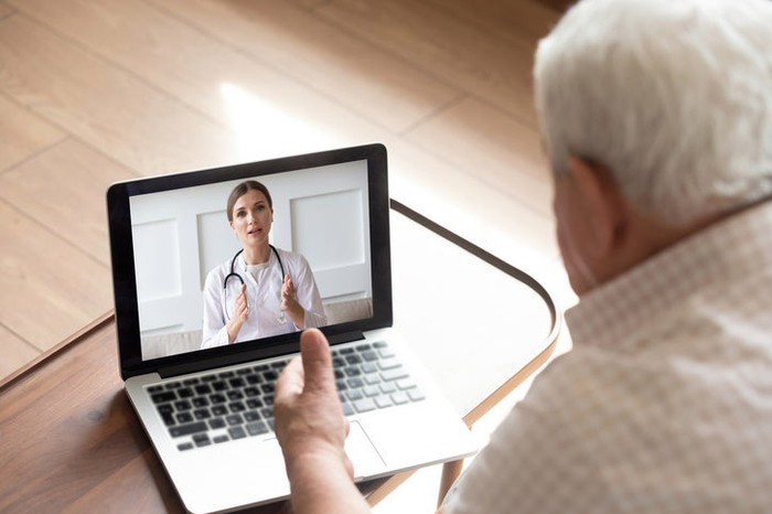 Older man using a laptop for a videoconferencing consultation with a younger female doctor.