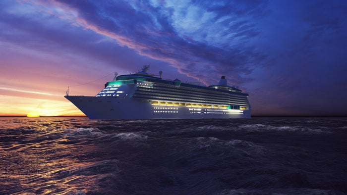 A cruise ship on the seas as day fades to  night and the lights come on in the ship.