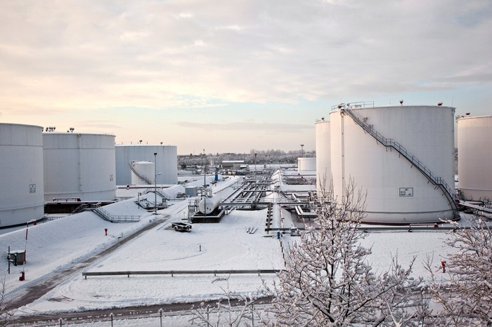 White petroleum storage tanks in the snow.