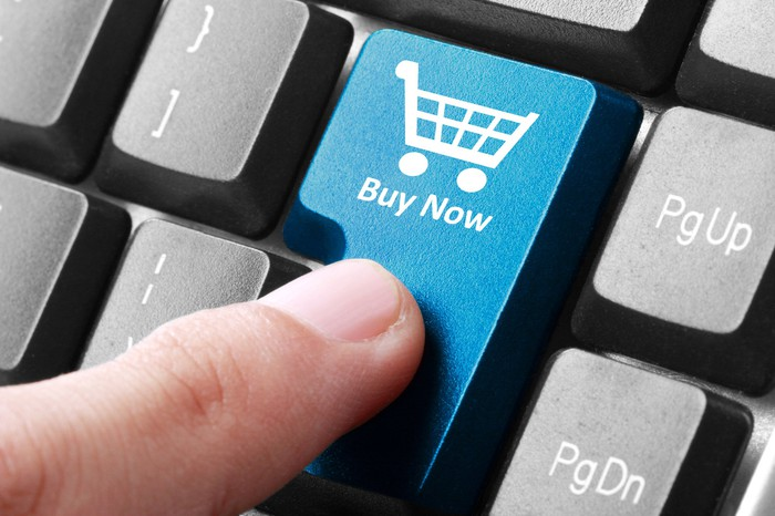 A finger pushes a buy now button on a keyboard with a picture of a shopping cart on it.