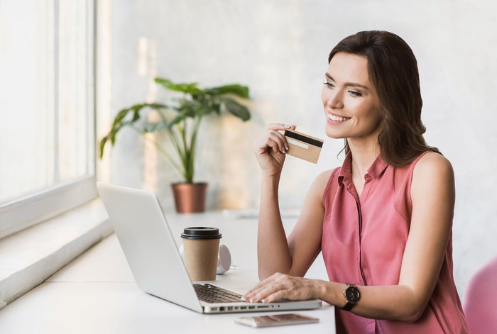 Smiling woman holding a credit card while sitting in front of a laptop