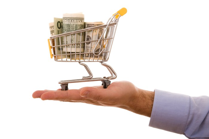 A small shopping cart with cash in it sitting on top of a man's palm