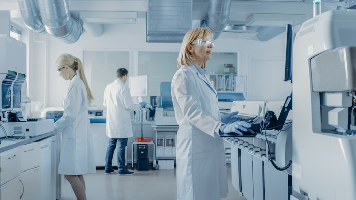 Three people in white lab coats working in a laboratory