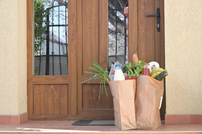 Two grocery bags stuffed with leafy vegetables sit on someone's front porch