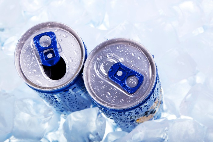 Two energy drinks surrounded by ice cubes