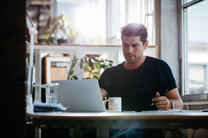 Man with serious expression at laptop.