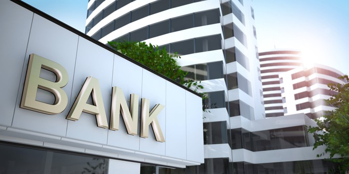 "The front of a bank with the word ""bank"" across the front with buildings in the background"